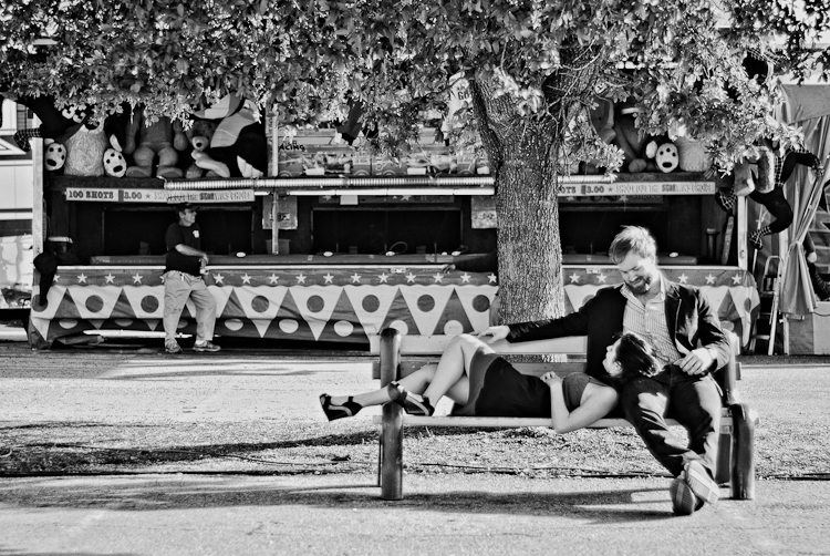 couple relaxing on bench engagement session in black and white