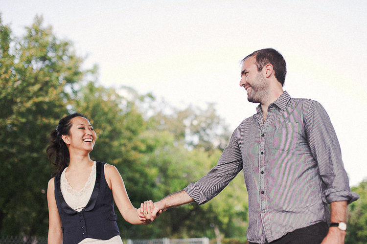 couple laughing and holding hands on train tracks engagement photos dc