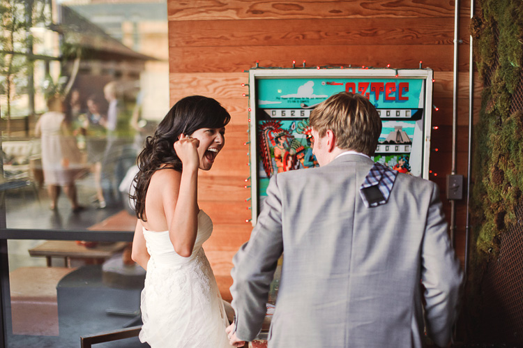 bride and groom playing pinball hipster