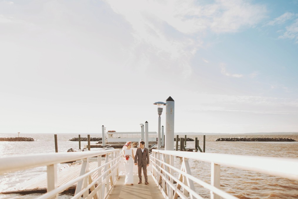 bride and groom walking on dock at adventure camp