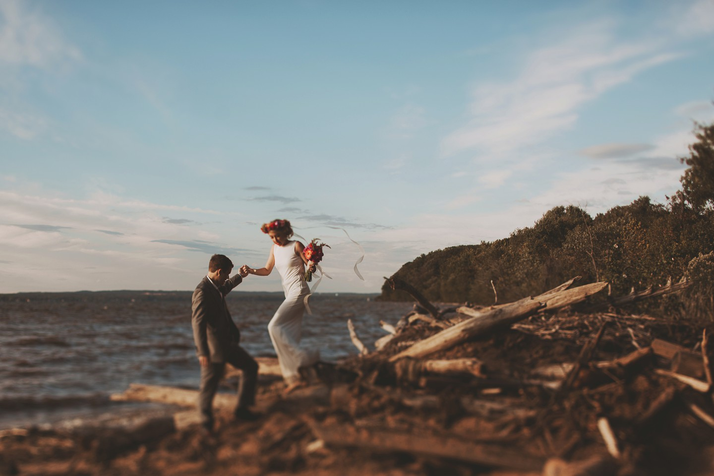 groom helping bride step down from pile of sticks