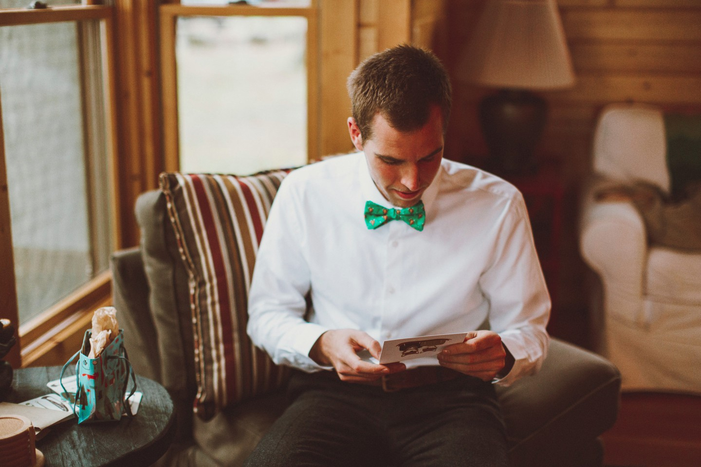groom reading in green bowtie