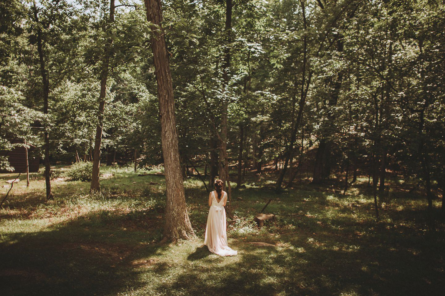 bride waiting for first look in forest