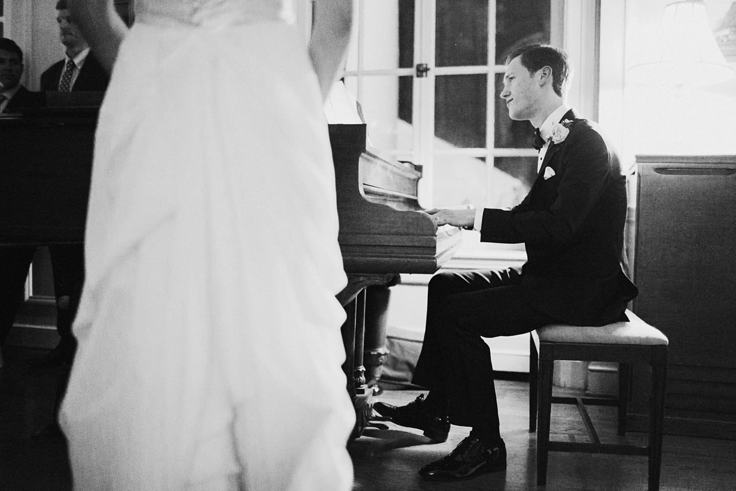 groom playing piano at strong mansion
