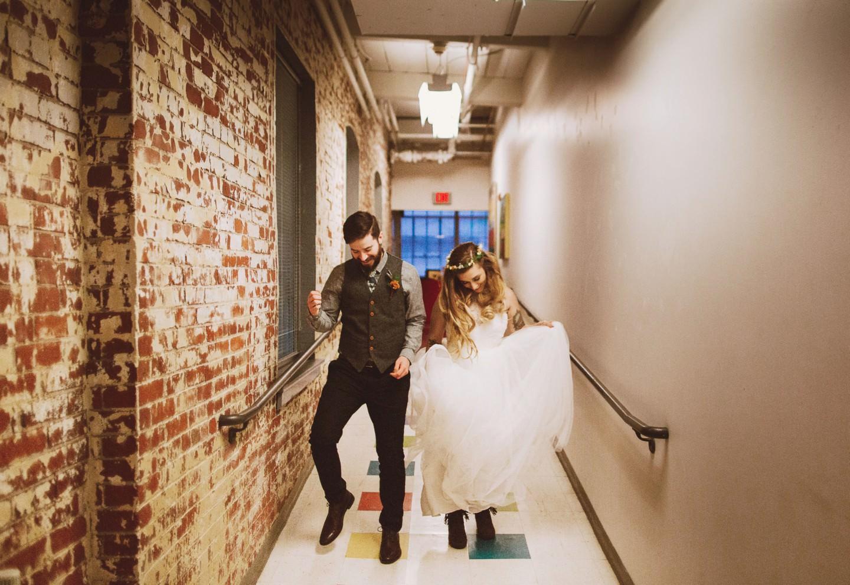 bride and groom dancing in a hallway